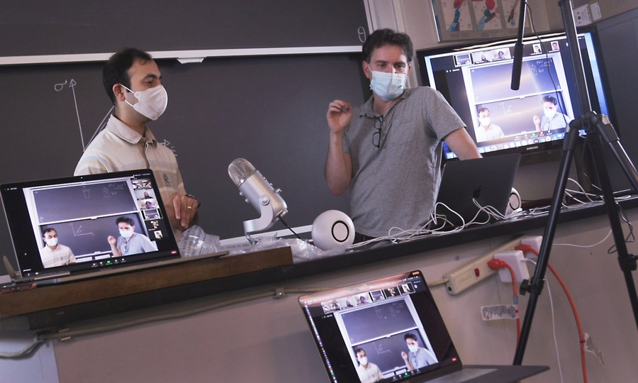 Rohit Karnik and Ken Kamrin, both wearing face masks, stand in front of a blackboard with laptop computers
