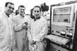 MIT researchers have developed a microchip that releases chemicals on demand. Here Professor Michael Cima, Graduate Student John Santini, and Professor Robert Langer stand in the MIT Microsystems Technology Laboratory where the chip was fabricated. Mr. Santini holds a silicon wafer containing 21 of the dime-sized chips.