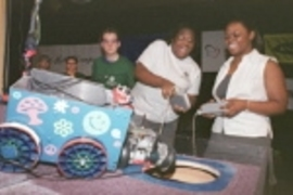 "Jasmine Richards (right) helps Kiwah Kendrick (left) operate her decorative ""Lady K"" vehicle while Micah Smith, a graduate student and judge, looks on during the annual Design 2.007 robot contest."