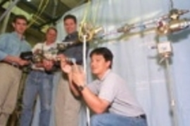 MIT researchers in the Department of Aeronautics and Astronautics stand with the instrumented truss that is key to the first hands-on experiment aboard the International Space Station. Left to right are Sophomore Cemocan Yesil, Associate Professor David Miller, Postdoctoral Fellow Gregory Mallory, and Graduate Student Jeremy Yung.