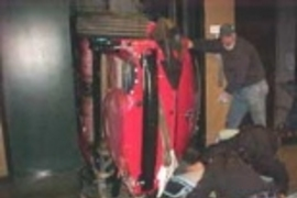 Workers load the car into an elevator shaft.