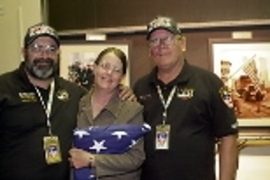 New York firefighters Mike Bellone (left) and Bob Barrett gave an American flag to Gayle Willman (center), who organized trips to Ground Zero for MIT volunteers to care for recovery workers. Behind them are photos taken at the World Trade Center disaster site.