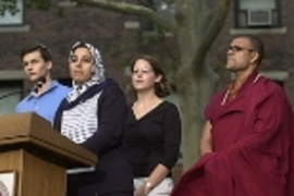 Representing their faiths at the podium are (left to right) Andrew Goldsweig, a Jewish senior in chemistry; Sarah Saleh, a Muslim graduate student in aeronautics and astronautics; Maureen Long, a graduate student in earth, atmospheric and planetary sciences, representing Christian traditions; and Buddhist Priyadarshi Shukla of the Harvard Divinity School.