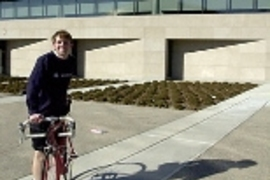 Cancer survivor Kyle Rattray stands next to his bike outside the Zesiger Center. He and a friend will be riding their bikes from Boston to Seattle this summer to raise money for the American Cancer Society.