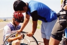 Taku Iida (standing) helps Kyle Rattray repair his second flat tire, just outside Billings, Mont.