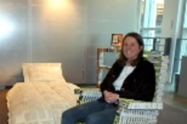 Stephanie Hartman relaxes in a rocking chair she made out of campus phone directories, part of a book-based bedroom suite on view in Rotch Library.