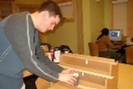 Will Etheridge sets up a beam-bending demonstration using a solid piece of wood (top), five bonded wooden strips (middle) and five unbonded strips.