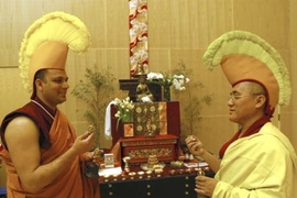 Adorned with hats to show discipleship, MIT Chaplain Tenzin L.S. Priyadarshi, left, and Lama Dhondup Tsering ring ceremonial bells representing compassion at Simmons Hall Monday in the room where the sand mandala is on display.