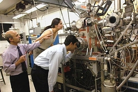 Senior research scientist Jagadeesh Moodera, left, points to the molecular beam epitaxy setup he uses in his research. With him are Tiffany Santos, graduate student in materials science and engineering, and postdoctoral associate John Philip.