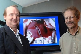 MIT research scientist Rutledge Ellis-Behnke, left, and Professor Gerald Schneider bracket a monitor showing a transected liver after it has been treated with a liquid solution containing peptides. The peptides self-assemble into a gel that essentially seals over the wound. The two developed the technique with MIT colleagues and researchers at the University of Hong Kong.