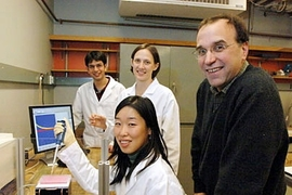 A team of MIT researchers is working on an implantable chip that can track whether a person is responding to cancer chemotherapy treatment. Standing, from left to right, are graduate student Christophoros Vassiliou, graduate student Karen Daniel and Michael Cima, professor of materials science and engineering. Seated in front is graduate student Grace Kim.
