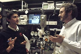 Graduate student Manu Prakash (left) and Professor Neil Gershenfeld discuss new applications for their microfluidic chips, which can carry on-chip process control information.