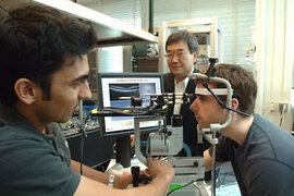 Professor James Fujimoto, center, with students using the eye-imaging technique he began developing in the early 1990s. With his head in the apparatus is Desmond C. Adler and at left, taking measurements, is Vivek Srinivasan. Adler and Sriinivasan are both graduate students in electrical engineering and computer science.