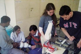 MIT students Maria Luckyanova and Philip Garcia (at right) operate their prosthetic-fitting device at the Jaipur Foot Organization headquarters in India in January, as JFO specialists work on fitting a prosthetic leg on a patient.
