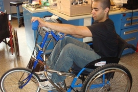 James Levi Schmidt, a member of an MIT class on wheelchair design for the developing world, tests a prototype of a wheelchair that was converted into a tricycle powered by hand-operated pedals.