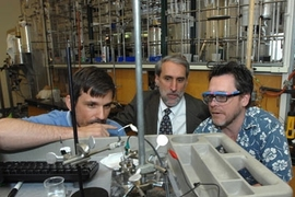 Chemistry professor Jonas Peters, Dan Nocera, Henry Dreyfus Professor of Energy, and Chris Cummins survey Nocera's piece of their solar energy work on artificial photosynthesis in Nocera's lab.
