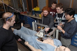 "Senior Paul Blascovich watches surgical robot operating from left, while teaching assistant Lael Odhner plays with arm. Junior Tony McDonald watches from back, Junior Ian Rust and instructor Harrison Chin watch from center and right of ""patient."""