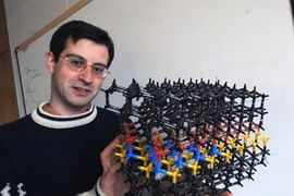 Mechanical Engineering Professor Tonio Buonassisi holds model illustrating problems with solar cells he is working on (in blue).