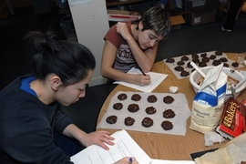 "Senior Angie Chiang, foreground, and junior Taylor Williamson write notes on the chemistry they have learned by making ""Death by Chocolate"" cookies in Patti Christie's Kitchen Chemistry course, offered in the ESG kitchen."