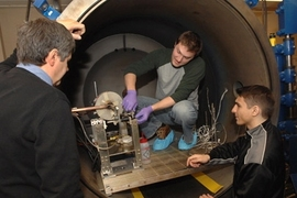 Department of Aeronautics and Astronautics graduate student Taylor Matlock, center, principal research scientist Oleg V. Batishchev, left, and Dan Stiurca, junior in electrical engineering and computer science, right, work on adjusting a prototype of a new plasma rocket.