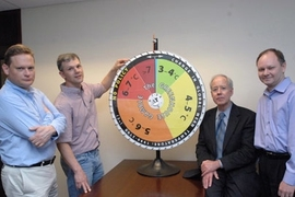 "Ronald Prinn, director of MIT's Center for Global Change Science, and his group have revised their model that shows how much hotter the Earth's climate will get in this century without substantial policy change. Standing with the group's ""roulette wheel"" are, from left to right, Mort Webster, professor in the Engineering Systems Division; Adam Schlosser, principal research scientist at the Center ..."