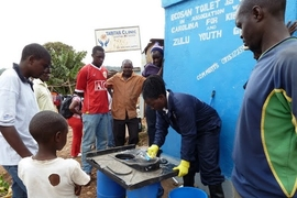 Community members attend a training session to learn how to keep the new Sanergy pilot toilets spotlessly clean.
