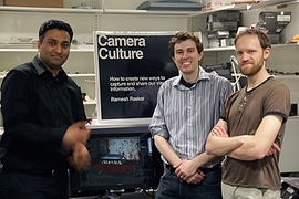 Associate Professor Ramesh Raskar, left, postdoc Douglas Lanman, center, and graduate student Matthew Hirsch flank the prototype of their new glasses-free 3-D video system.