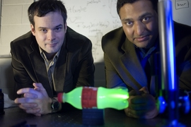Media Lab postdoc Andreas Velten, left, and Associate Professor Ramesh Raskar with the experimental setup they used to produce slow-motion video of light scattering through a plastic bottle.