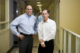 Professors Robert S. Langer (right) and Michael J. Cima speak in the Cima Lab at the David H. Koch Institute for Integrative Cancer Research at MIT. Langer and Cima work together in biotechnology and have developed a new implantable medical device which allows repeated wireless drug delivery in lieu of injections.