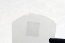 The researchers' membrane, consisting of graphene on a polycarbonate track etch membrane (the graphene is the darker region in the center of the white film). The total membrane is about 2 cm wide by 1 cm tall, while the graphene portion is about 5 mm by 5 mm.