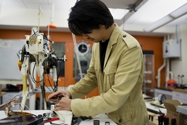 Assistant Professor Sangbae Kim works on the 70-pound 'cheetah' robot designed at MIT.