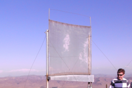 View of one of the test fog collectors set up by the MIT team in Chile, as it gathers water in the white plastic drum.