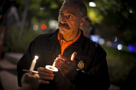 John DiFava, MIT's director of facilities operations and security, holds a candle during the moment of silence to honor slain MIT Officer Sean Collier.