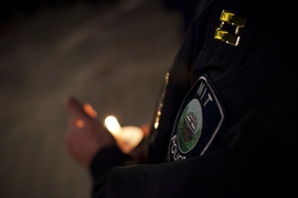 An MIT Police officer's badge is illuminated by candlelight.