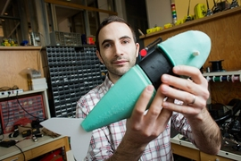 Andrew Marchese, doctoral candidate in EECS at MIT, holds a soft robotic fish developed by the Distributed Robotics Laboratory.