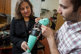 Andrew Marchese, doctoral candidate in EECS at MIT (right), and Dr. Daniela Rus, professor in EECS and Director of CSAIL, hold a soft robotic fish developed by the Distributed Robotics Laboratory.
