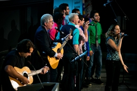 Collins (middle) sings with Pardis Sabeti (right), a Broad Institute researcher; guitarist Bob Katsiaficas (left); and the MIT Logarhythms a cappella group.