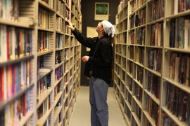 "D. W. Rowlands, president and ""skinner,"" goes through the stacks in the society library. The Society strives to acquire every new science-fiction publication for its collection, sometimes obtaining proofs before a book is officially published."