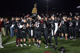 MIT players hold up the New England Football Conference trophy.