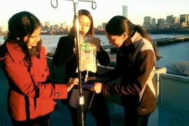 Gururaj and teammates test a device to warm IV fluid on the balcony of the McCormick Hall penthouse to see how the device performs in colder environments.