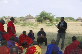 An employee of Global Cycle Solutions introduces a solar lamp to villagers in rural Tanzania.