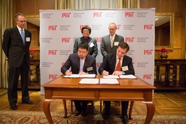 Samuel Tak Lee '62, SM '64 (standing, left) and MIT President L. Rafael Reif look on as Lee's son, Samathur Li, and MIT Executive Vice President and Treasurer Israel Ruiz sign documents related to Lee's $118 million gift to MIT.