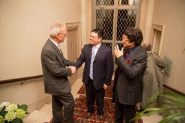 MIT President L. Rafael Reif greets Samathur Li (center) and Samuel Tak Lee at Gray House, where the signing ceremony was held.
