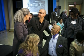 MIT professor of writing Junot Diaz converses with professor of linguistics Michel DeGraff (seated) and others at the annual Dr. Martin Luther King Jr. luncheon.