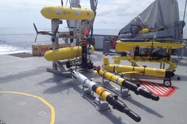 Several classes of autonomous underwater vehicles await deployment on the deck of the Falkor, off the coast of western Australia.