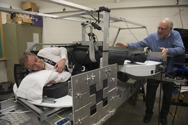 Swedish astronaut Christer Fuglesang tries out the new centrifuge while MIT professor Larry Young coaches him on.