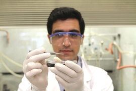 Seyed Mirvakili, lead author of the paper describing the niobium supercapacitors, examines a strand of the material in the lab.