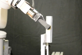 The robot pivots the rod between its fingers by pushing against a bookend.