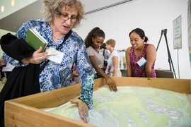 Attendees learn about various projects, including the AR Sandbox, a real-time topographical map made of moveable sand.