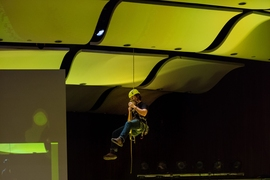 A student demonstrates a rappelling device for climbers by descending from the ceiling of Kresge.